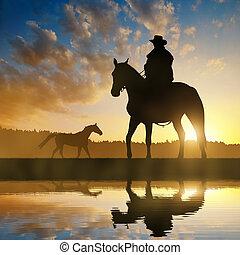 Silhouette Cowboy mit Pferd.