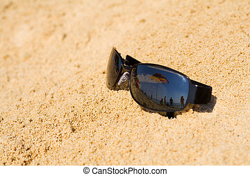 Sonnenbrille, die den Blick auf den Strand widerspiegelt.