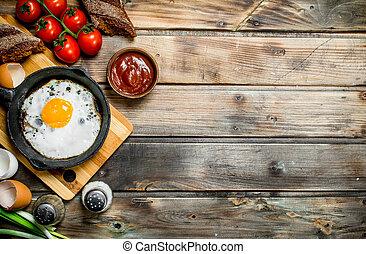 Spiegelei in einer Pfanne mit Brot, Tomaten und grünen Zwiebeln.