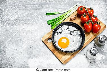 Spiegelei in einer Pfanne mit Tomaten und grünen Zwiebeln.