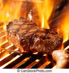 Steak auf dem Grill mit Flammen.