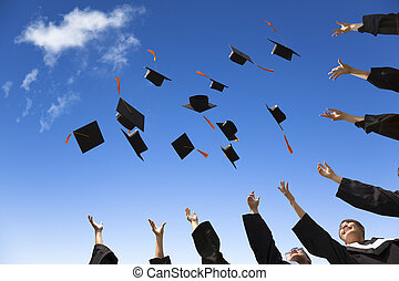 Studenten, die Abschlusshüte in der Luft feiern.