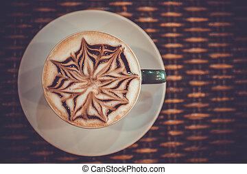 Tasse Kaffeekaffee mit Design-Kunst in Froth, auf einem Holztisch. Makro schließen