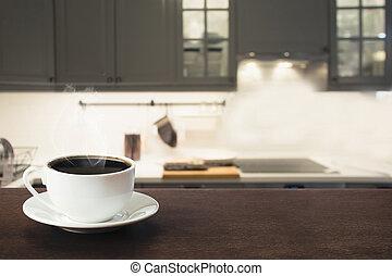 Tasse schwarzen Kaffee auf Holztischplatte in verschwommener, moderner Küche. Mach zu. Indoor.