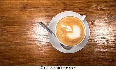 Top Aussicht auf Cappuccino Kaffee mit Kunstkleid in weißer Tasse auf poliertem Holztisch.