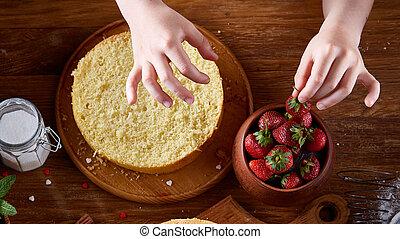 Top Blick auf die Hände von Mädchen, die einen Kuchen mit Erdbeeren dekorieren, eng, selektiv, vertikal.
