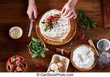 Top Blick auf die Hände von Mädchen, die Erdbeeren auf Kuchen, Nahaufnahme, vereinzelte Konzentration, vertikal.