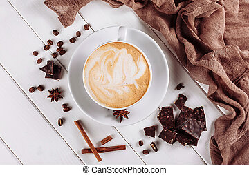 Top Blick auf Latte heißen Kaffee oder Cappuccino in weißer Tasse mit Kunstschaum und gebratenen Kaffeebohnen auf Holztisch Hintergrund.