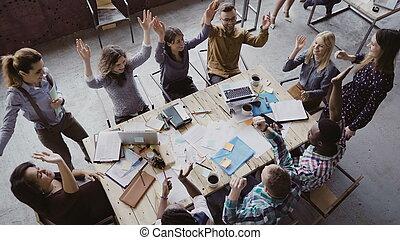 Top View of business team working at trendy Loft office. Die junge gemischte Rassengruppe setzt Hand in Hand.