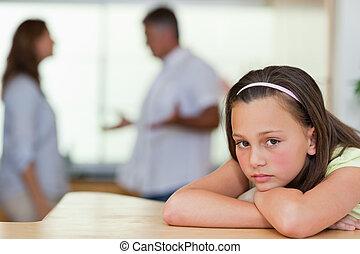 Trauriges Mädchen mit kämpfenden Eltern hinter sich
