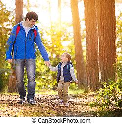 Vater und Sohn wandern im Herbstwald.