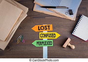 Verloren, verwirrt und verwirrt. Papierschild auf einem Holztisch