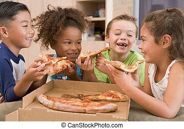 Vier junge Kinder im Haus essen Pizza lächelnd.