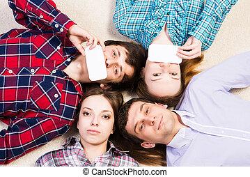 Vier junge Männer liegen zusammen.