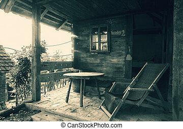 Vor einem Holzhaus.