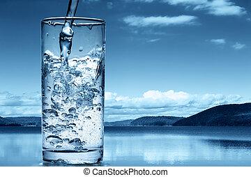 Wasser in ein Glas vor der Natur zu gießen