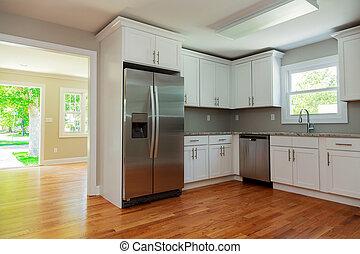 Weiße Küche mit Waschbecken, Schränke und Holzböden.