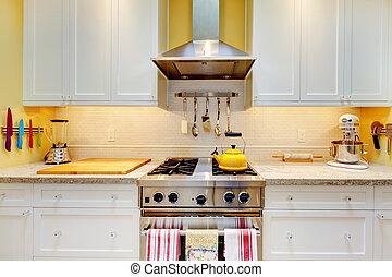 Weiße Küchenschränke mit Herd und Kapuze.
