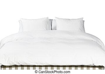 Weiße Kissen und Decke auf einem Bett.