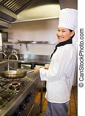 Weibliche Köchin bereitet Essen in Kitsch vor.