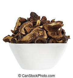Wilde und getrocknete Pilze in einer weißen Schüssel.