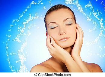 Wunderschöne junge Frau, die ihr Gesicht wäscht