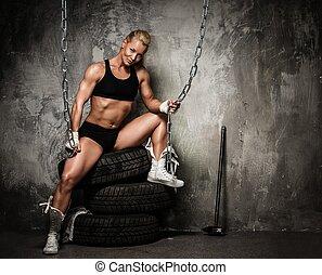 Wunderschöne Muskel-Körperbauerin, die auf Reifen sitzt und Ketten hält.