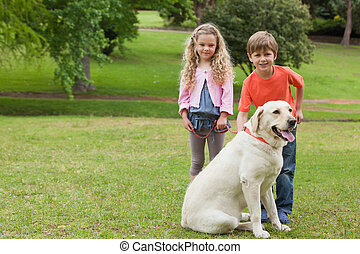 Zwei Kinder mit Hund im Park.